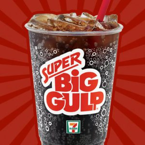 A Super Big Gulp soda against a reddish background