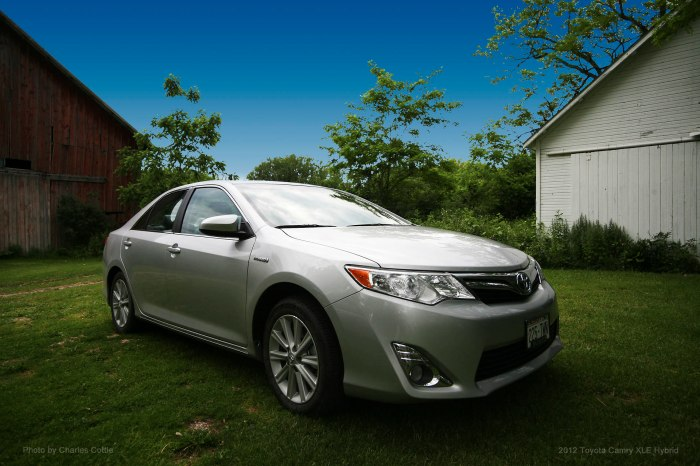 Silver Toyota Camry Hybrid framed by barns in the background
