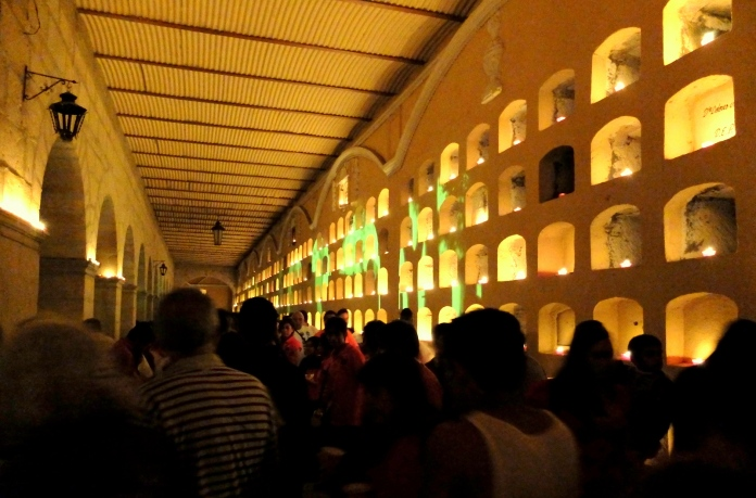 Night scene with candles illuminating a wall of tombs at the main cemetery in the city of Oaxaca.