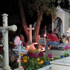 Night scene of family at a grave site in the main cemetery of the city of Oaxaca.