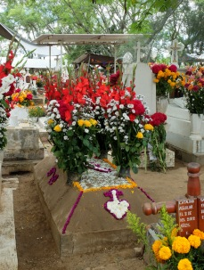 Flowers decorate the sand structure on this view of a grave site at San Antonín