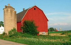 A traditional red barn with a stone foundation in the foreground with similar structures in the background a half mile away.