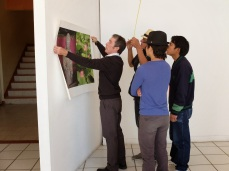 Professor Flanagan instructs students in how to hang an exhibit