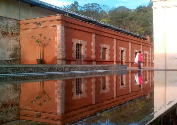 A reflecting pool en front of a low  reddish adobe colored building.