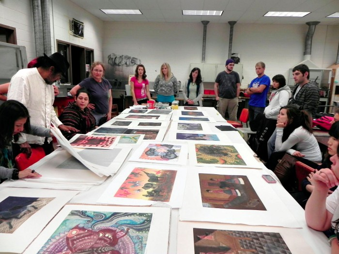 Maestro Juan Alcázar laying out large prints on a reviewing table with student looking on.