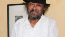 Portrait of Maestro Juan Alcázar. He is wearing a white guayabera and a dark hat.