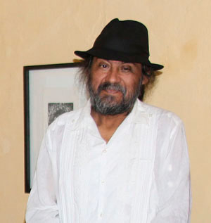 Portrait of Maestro Juan Alcázar. He is wearing a white guayabera and a dark hat.