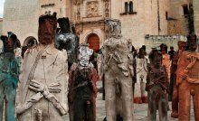 An assembly of clay sculptures of migrants standing in front of 17th century church in Oaxaca