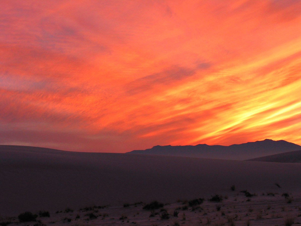 Vibrant sunset with dunes in foreground