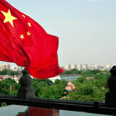 In the foreground a Chinese flag flutters in the wind looking toward skyscrapers in the distance.