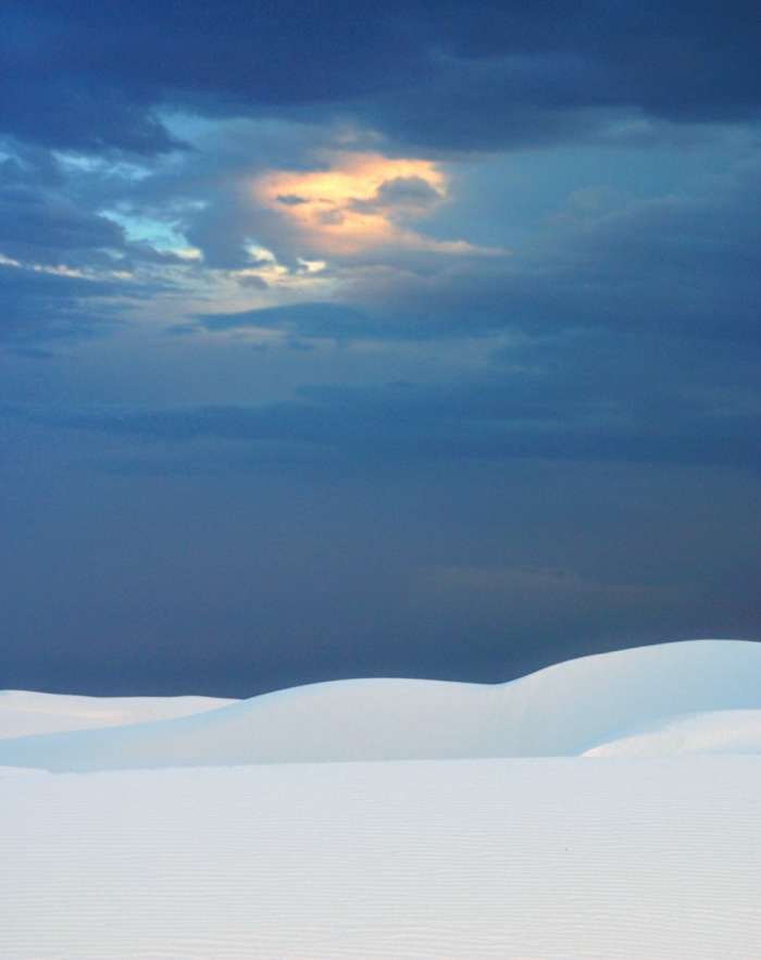 White sand dunes against a dark sky near sunset