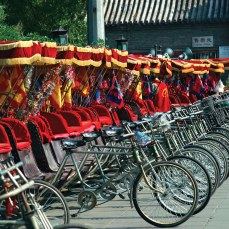 A line of parked bicycle rickshaws with red seats and canopies.